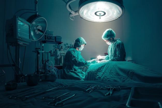 Équipe de chirurgiens travaillant avec surveillance du patient en salle d'opération chirurgicale. Photo Premium