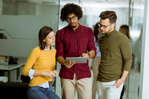 Équipe commerciale multiethnique utilisant une tablette numérique dans le bureau d'une petite entreprise en démarrage Photo Premium