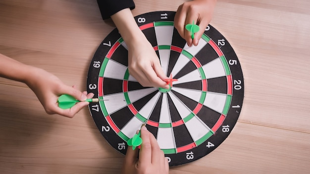 Équipe commerciale pointant vers un jeu de fléchettes visant le centre d'affaires cible Photo Premium