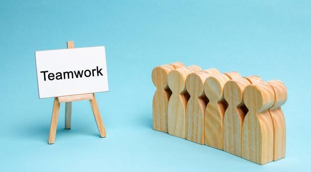 L'équipe commerciale se tient près de la toile avec le mot travail d'équipe. concept de travail d'équipe. Photo Premium