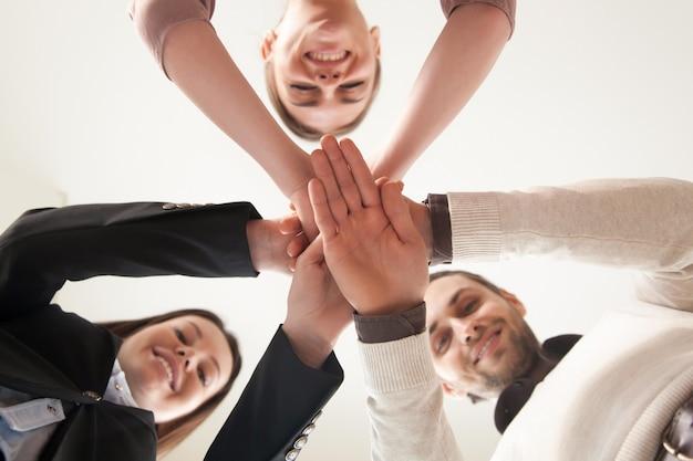 Équipe commerciale unie qui réussit à réunir les mains, vue d'en bas Photo gratuit
