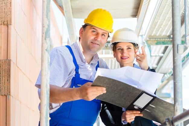Équipe de construction avec plans de construction sur le site Photo Premium
