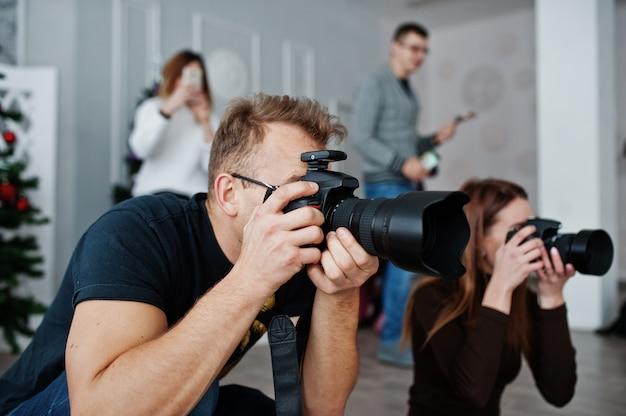 L'équipe De Deux Photographes Photographiant En Studio Derrière Trois Autres Travailleurs. Photographe Professionnel Au Travail. Cours De Maître. Photo Premium