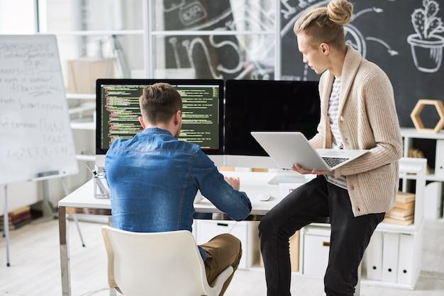 Équipe De Développement Discutant Du Code Informatique Photo Premium