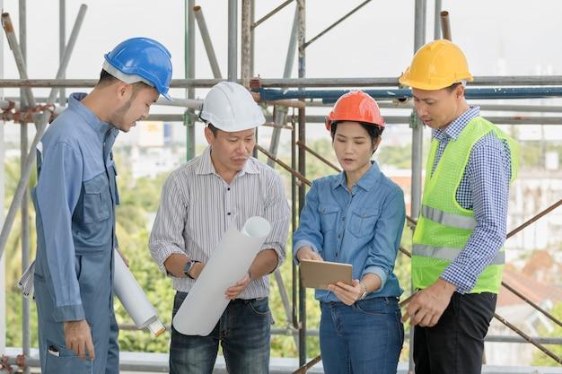 Équipe d'ingénieurs et d'architectes discutant de la mise en page d'un ordinateur tablette sur le chantier Photo Premium
