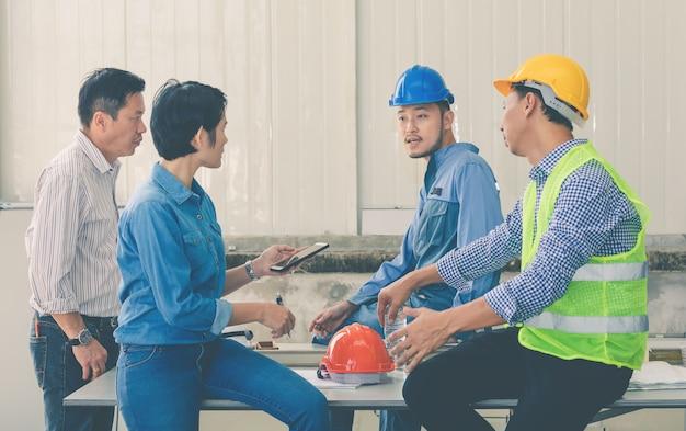 Équipe d'ingénieurs et d'architectes discutant des travaux de construction sur le chantier Photo Premium