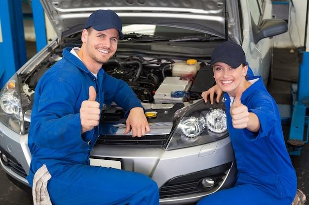 Équipe de mécaniciens souriant à la caméra Photo Premium