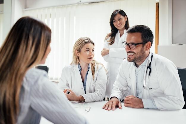 Équipe de médecins annonçant de bonnes nouvelles à une patiente. Photo Premium