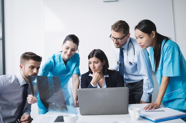 Équipe Médicale Examinant Un Rapport De Radiographie Photo gratuit