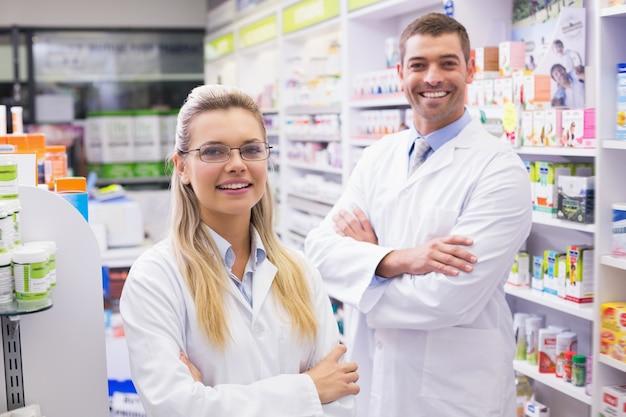 Équipe de pharmaciens souriant à la caméra à la pharmacie de l'hôpital Photo Premium
