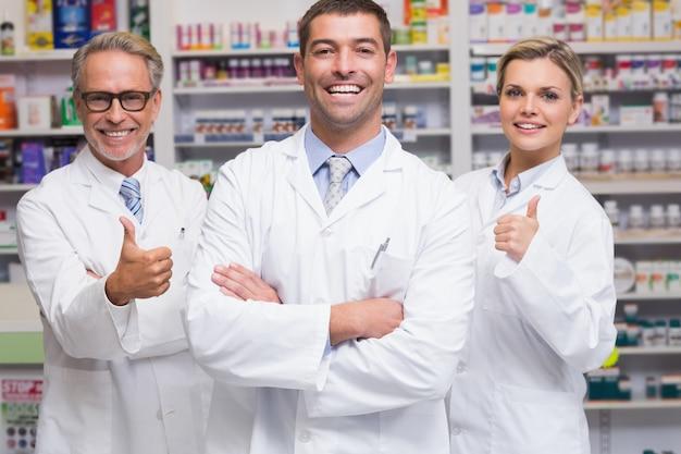 Équipe de pharmaciens souriant à la caméra à la pharmacie Photo Premium