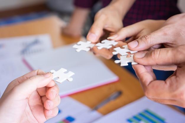 Équipe plaçant quatre puzzles ensemble pour le concept d'équipe Photo Premium