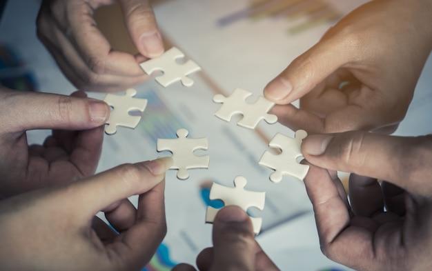 Équipe plaçant six puzzles ensemble pour le concept d'équipe Photo Premium