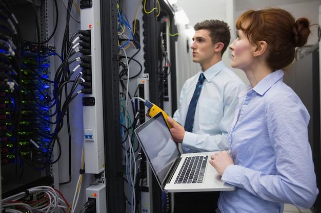 Équipe de techniciens utilisant un analyseur de câble numérique sur des serveurs Photo Premium