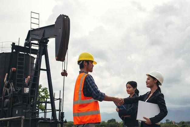 L'équipe technique se tient à côté de pompes à huile fonctionnant avec un ciel. Photo gratuit