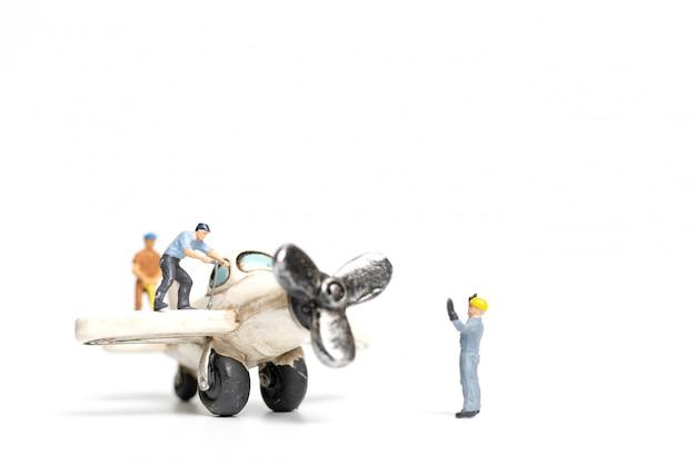 Équipe de travailleurs réparant un avion jouet sur fond blanc Photo Premium