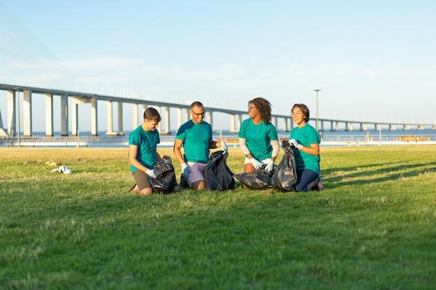 Équipe de volontaires interraciaux ramassant les ordures de la pelouse Photo gratuit