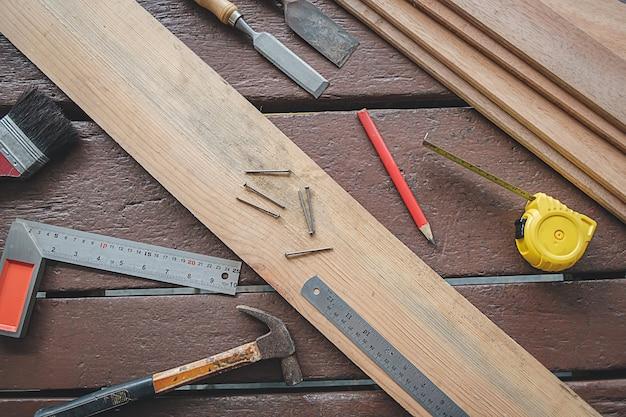Équipement sur un bureau en bois avec homme travaillant dans le fond de l'atelier. Photo Premium