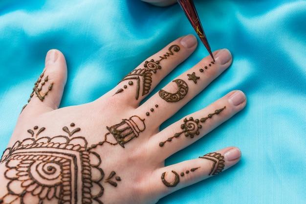 L'équipement pour le tatouage mehndi dessine près de la main de la femme Photo gratuit
