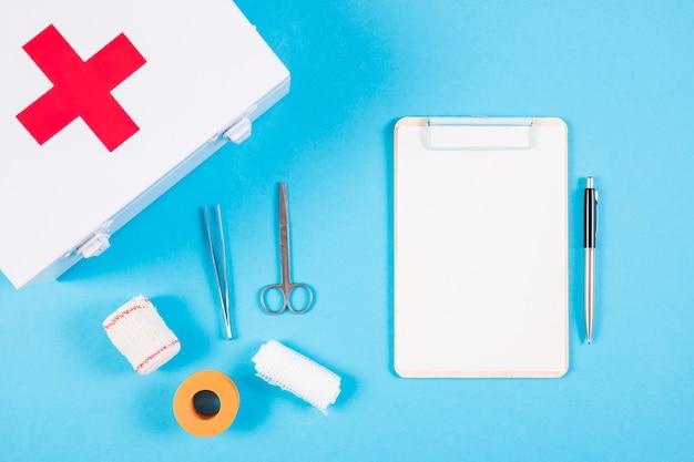 Équipements médicaux; trousse de premiers secours; presse-papiers et stylo sur fond bleu Photo gratuit