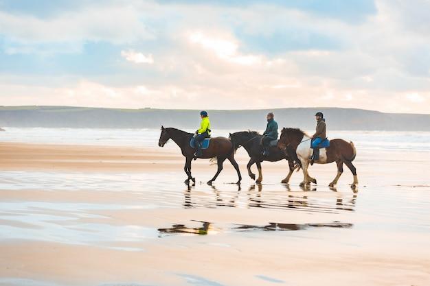 Équitation sur la plage au coucher du soleil au pays de galles Photo Premium