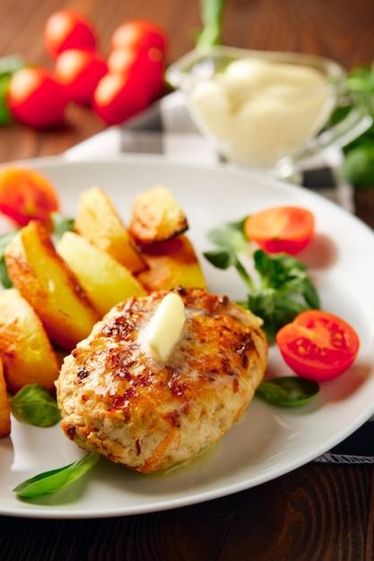 Escalope de poulet frit avec des tranches de pommes de terre servies avec une salade de tomates cerises et de maïs. Photo Premium
