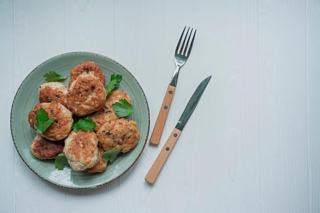 Escalopes aux herbes servies sur une assiette sur un fond en bois blanc. Photo Premium