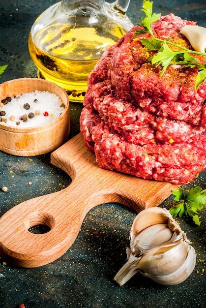 Escalopes de burger crues avec sel, poivre, huile, herbes et épices Photo Premium
