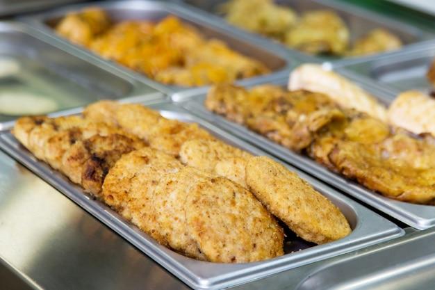 Escalopes et plats de viande au buffet sur des assiettes en métal. mise au point sélective Photo Premium