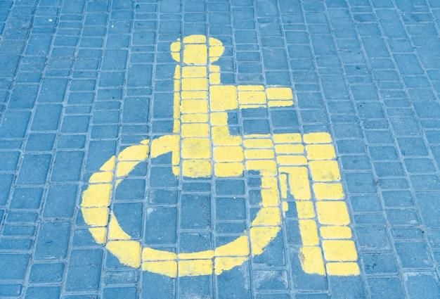 L'espace de stationnement de voitures pour personnes handicapées le signe dessiné sur la tuile de la route. Photo Premium