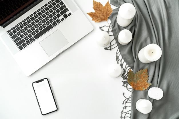 Espace de travail de bureau à domicile avec téléphone portable et écran blanc, ordinateur portable, ordinateur portable, écharpe, bougies, feuilles sur blanc Photo Premium