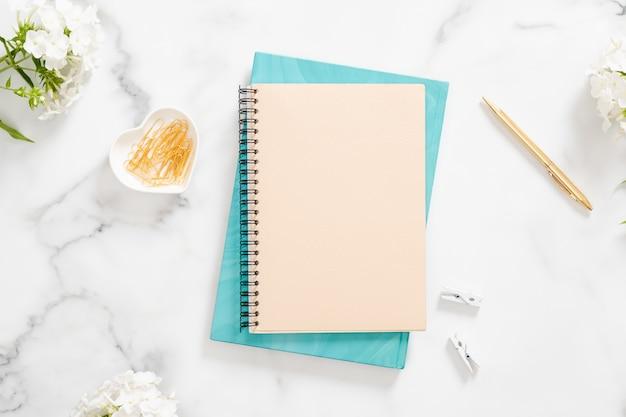 Espace de travail de bureau moderne avec un cahier vierge, des fleurs blanches et des accessoires féminins Photo Premium