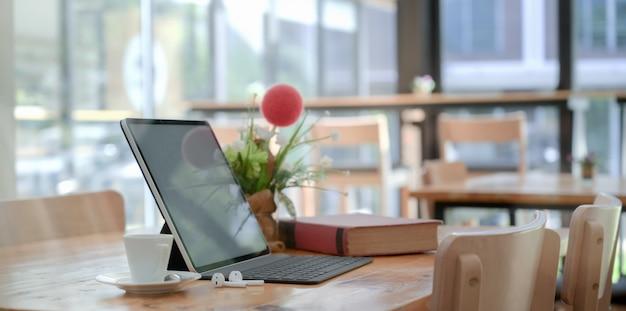 Espace de travail confortable avec tablette avec clavier et livre, décorations et tasse de café Photo Premium