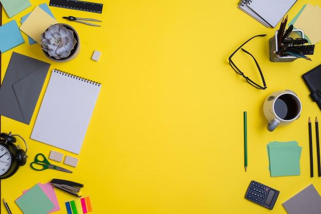 Espace de travail contemporain avec fournitures sur fond jaune Photo gratuit