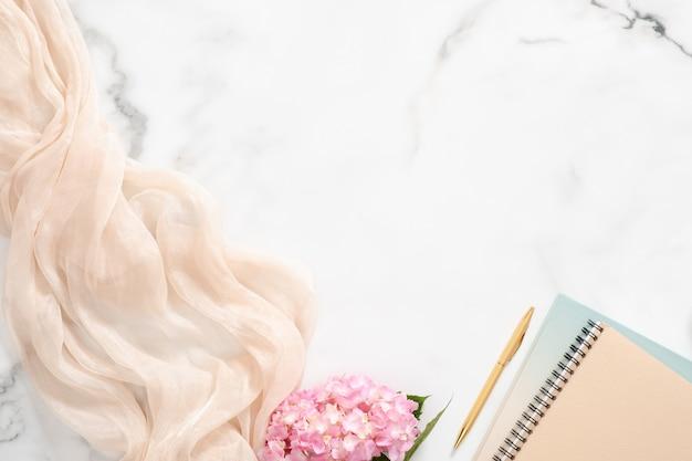 Espace de travail féminin avec fleur d'hortensia rose, couverture pastel, bloc-notes en papier et accessoires sur fond de marbre Photo Premium