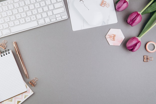 Espace de travail féminin avec tulipes, clavier, pinces dorées sur fond gris Photo Premium