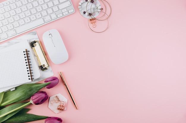 Espace de travail féminin avec tulipes, clavier, pinces dorées sur rose Photo Premium