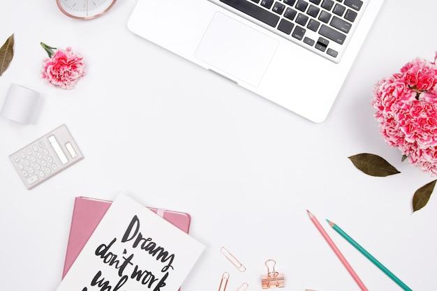 Espace de travail femme avec ordinateur portable, cahier, fleur oeillet rose, smartphone Photo Premium