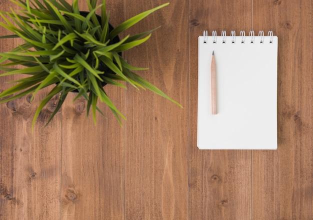 Espace de travail minimal, cahier et crayon brun sur fond de table en bois Photo Premium