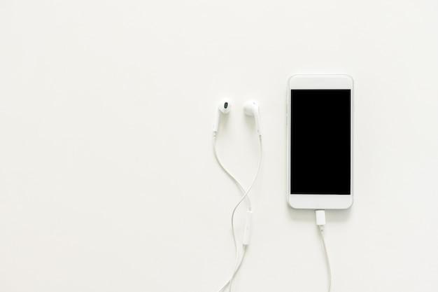 Espace de travail minimal - photo de bureau de bureau créative créative avec écouteurs et téléphone mobile avec écran vierge sur fond blanc de copie. vue de dessus maquette, photographie plate. Photo Premium