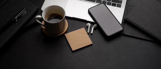 Espace De Travail Moderne Sombre Avec Ordinateur Portable, Smartphone, Tasse à Café, écouteurs, Bloc-notes Et Espace De Copie Photo Premium