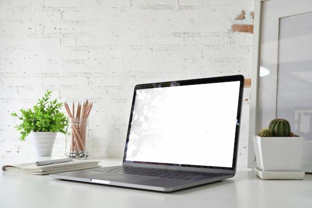 Espace De Travail Avec Un Ordinateur Portable à écran Blanc Vierge Sur Le Bureau Loft. Photo Premium
