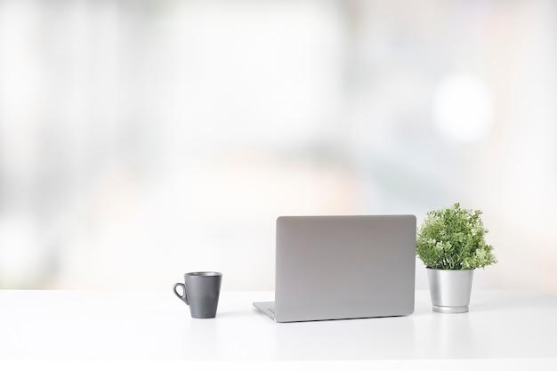 Espace de travail avec ordinateur portable et tasse à café et plante, concept de travail de bureau élégant. Photo Premium