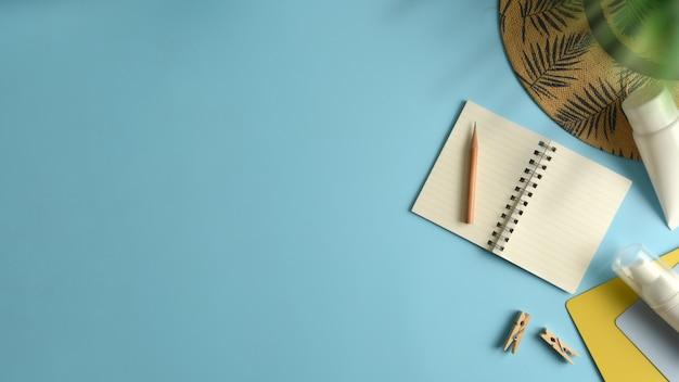 Espace de travail vue de dessus plat avec chapeau, bloc de soleil sur fond bleu. Photo Premium