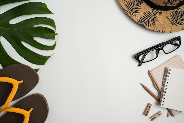 Espace de travail vue de dessus plat avec lunettes, cahier, chapeau, crayon, feuille verte, chaussures et tasse à café sur fond blanc. Photo Premium