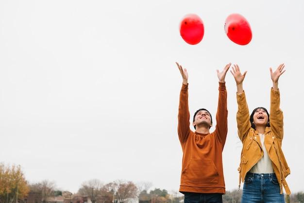 Espiègle jeune couple lâcher des ballons Photo gratuit
