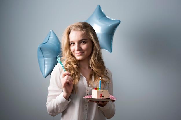 Espiègle jeune femme manger un gâteau d'anniversaire Photo gratuit