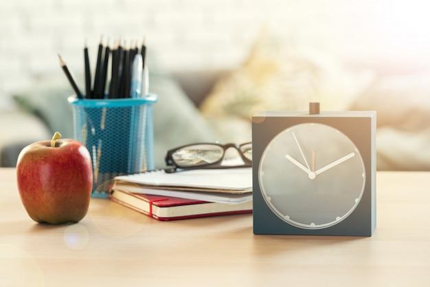 C'est l'heure de l'école, réveil vintage et pomme sur un bureau en bois Photo Premium