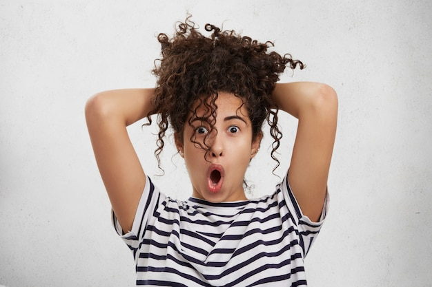Est-ce Vraiment La Vérité? Surpris Femme étonnée Garde Les Mains Derrière La Tête, Regarde Avec La Bouche Largement Ouverte Photo gratuit