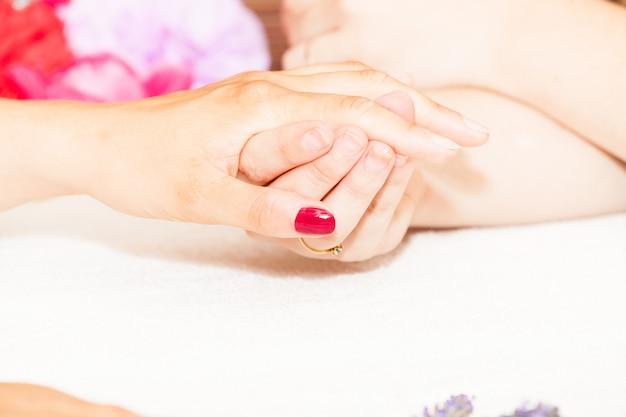 L'esthéticienne décore de fleurs les ongles des mains du client Photo Premium